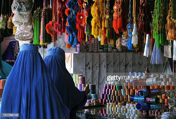Afghan burqaclad women refugees inspect bangles on display at a shop in Peshawar on June 19 2010 As Pakistan continues its costly fight against...