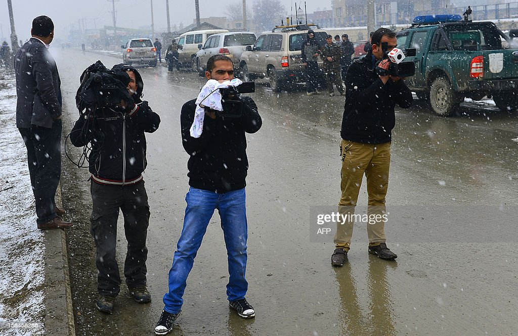 Afghan cameramen film near the site of an explosion in Kabul on December 17, 2012. A car bomb exploded at a compound owned by a US-based construction company under contract to the Afghan army, killing at least one person and wounding 15, police said. Five foreigners including some from the US and South Africa were among the wounded, a security source at the company told AFP. AFP PHOTO/ Massoud HOSSAINI