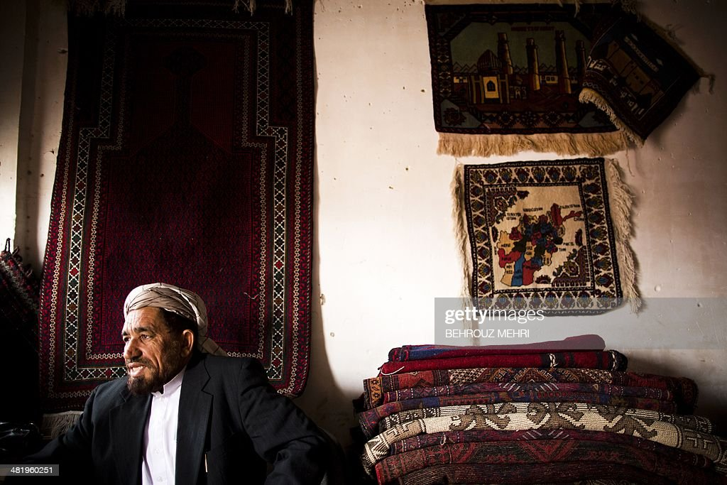 Afghan carpet seller Haji Abdolbaghi, who sells Afghan hand-made carpets, sits alongside a rug bearing a map of Afghanistan at his carpet shop in the northwestern city of Herat on April 2, 2014. Carpets are Afghanistan's best-known export, woven mostly by women and children in the north of the country, a trade which once employed, directly or indirectly, six million people, or a fifth of the country's population, but that figure has dropped sharply.
