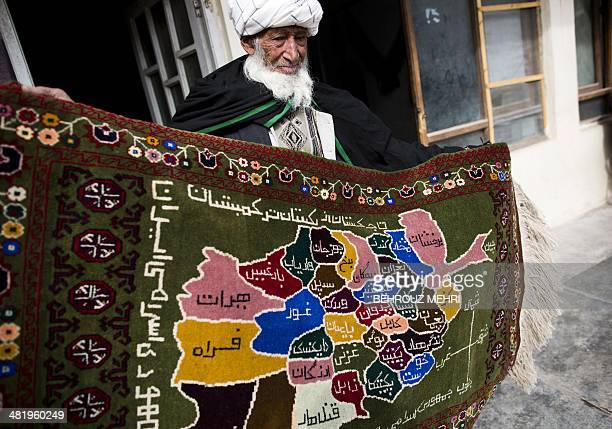 Afghan carpet seller Jahangir holds up a rug bearing a map of Afghanistan at a carpet shop in the northwestern city of Herat on April 2 2014 Carpets...