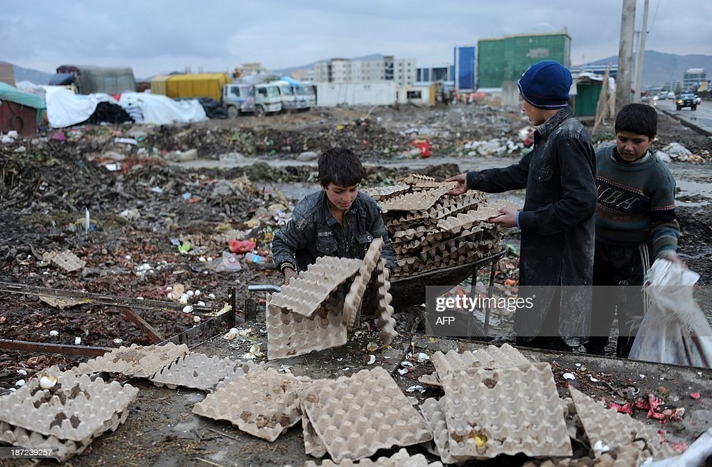 Afghan child labourers collect cardboard and other materials from a rubbish dump to be used as firewood as winter begins in Kabul on November 7, 2013. Tens of thousands of children in Afghanistan, driven by poverty, work on the streets of the war-torn country's cities and often fall prey to Taliban bombings and other violence, as well as abuse. AFP PHOTO/ FARSHAD USYAN