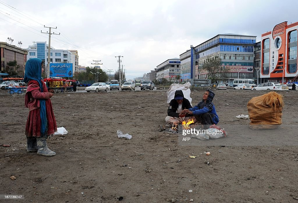 Afghan child labourers sit around a fire on the roadside as winter begins in Kabul on November 7, 2013. Tens of thousands of children in Afghanistan, driven by poverty, work on the streets of the war-torn country's cities and often fall prey to Taliban bombings and other violence, as well as abuse.