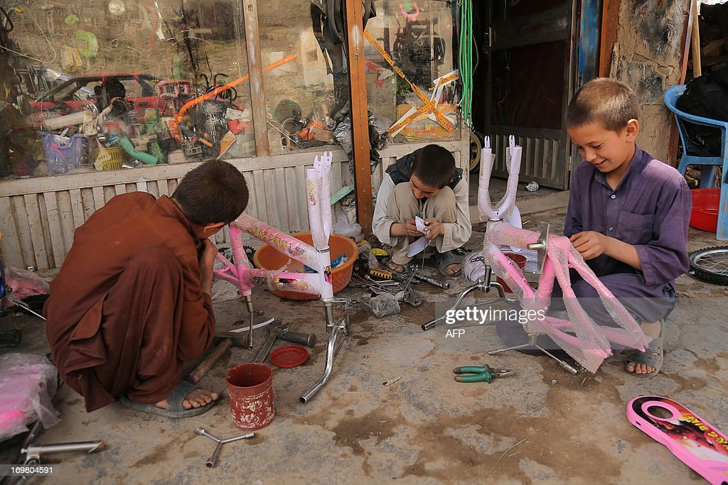 Afghan child labourers work at a bicycle mechanic shop in Ghazni on June 2, 2013. Tens of thousands of children in Afghanistan, driven by poverty, work on the streets of the war-torn country's cities and often fall prey to Taliban bombings and other violence, as well as abuse. AFP PHOTO/ Rahmatullah ALIZADA