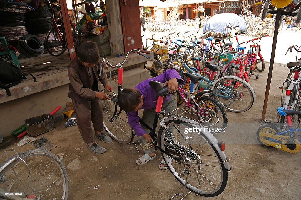 Afghan child labourers work at a bicycle shop in Ghazni on June 2, 2013. Tens of thousands of children in Afghanistan, driven by poverty, work on the streets of the war-torn country's cities and often fall prey to Taliban bombings and other violence, as well as abuse. AFP PHOTO/ Rahmatullah ALIZADA