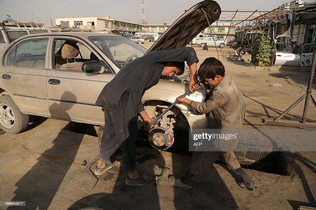 Afghan child labourers work at a mechanic shop in Ghazni on June 2, 2013. Tens of thousands of children in Afghanistan, driven by poverty, work on the streets of the war-torn country's cities and often fall prey to Taliban bombings and other violence, as well as abuse. AFP PHOTO/ Rahmatullah ALIZADA