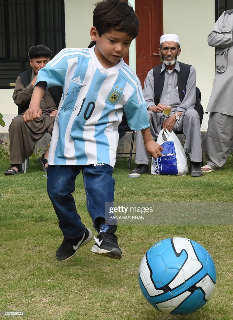 Afghan child Murtaza Ahmadi, 5, and a fan of football player Lionel Messi, plays with a football while wearing a shirt donated and signed by Messi in Pakistan's southwestern city of Quetta on May 3, 2016. The young Afghan boy who captivated hearts after he was pictured wearing a plastic bag as an improvised Lionel Messi jersey has appealed to the UN refugee agency after fleeing Afghanistan. Murtaza Ahmadi became an Internet sensation in January after his older brother posted the picture on Facebook, with the Argentine superstar sending autographed jerseys to his tiny fan via UNICEF. KHAN