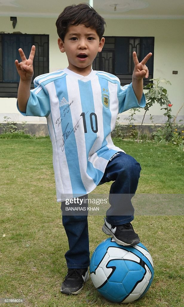 Afghan child Murtaza Ahmadi, 5, and a fan of football player Lionel Messi, poses for a photograph as he plays with a football while wearing a shirt donated and signed by Messi in Pakistan's southwestern city of Quetta on May 3, 2016. The young Afghan boy who captivated hearts after he was pictured wearing a plastic bag as an improvised Lionel Messi jersey has appealed to the UN refugee agency after fleeing Afghanistan. Murtaza Ahmadi became an Internet sensation in January after his older brother posted the picture on Facebook, with the Argentine superstar sending autographed jerseys to his tiny fan via UNICEF. KHAN