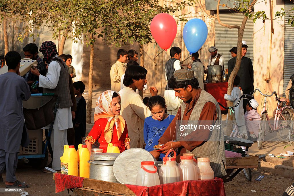Afghan children buy peas from a vendor at a fair in Herat on October 28, 2012, during Eid al-Adha. Afghans started celebrating Eid al-Adha or 'Feast of the Sacrifice', which marks the end of the annual hajj or pilgrimage to Mecca and celebrated in remembrance of Abraham's readiness to sacrifice his son to God. AFP PHOTO/Aref Karimi