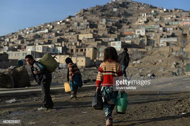 Afghan children carry cans of water through a cemetery in Kabul on January 14 2014 Economic development is considered a vital weapon to stop the...