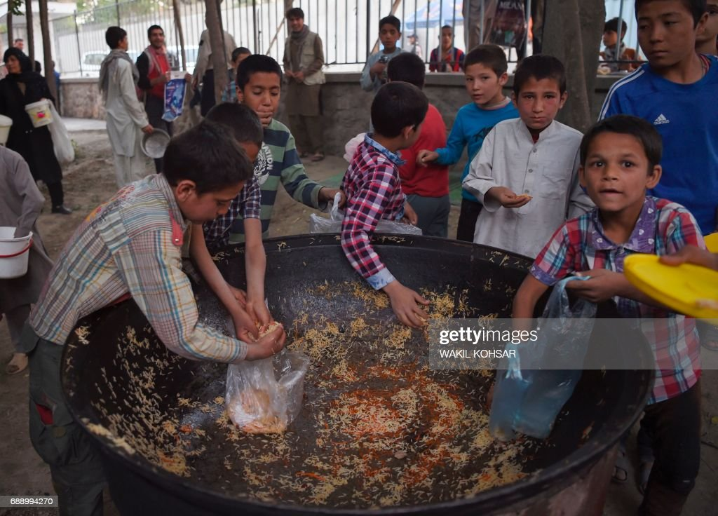 Afghan children collect rice as they receive food donated by private charity for the poor people during the first day of the Islamic holy month of Ramadan at the Wazir Akbar Khan Mosque on May 27, 2017 in Kabul. Muslims throughout the world are marking the month of Ramadan, the holiest month in the Islamic calendar during which devotees fast from dawn till dusk. /