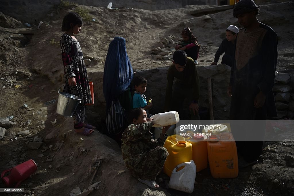 Afghan children fill water containers from a tap during the Islamic holy month of Ramadan in the old section of Kabul on June 26, 2016. Muslims throughout the world are marking the month of Ramadan, the holiest month in the Islamic calendar during which devotees fast from dawn till dusk. / AFP / WAKIL
