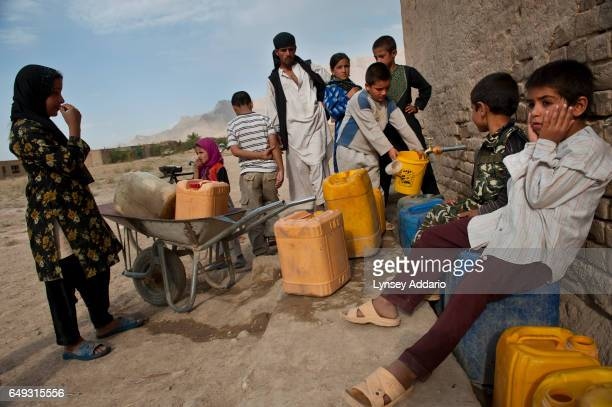 Afghan children fill water jugs from the only water spout in the mostly abandoned land allocation settlement of AliceGhan about 30 miles outside of...