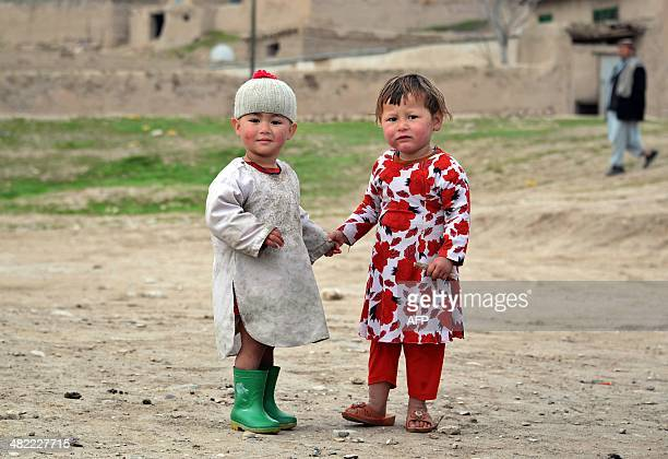 Afghan children look on as they walk in their neighborhood in the Kishindih district of northern Balkh Province on April 3 2014 Afghans will go to...