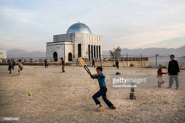 Afghan children play cricket as other play soccer at Teppe Maranjanin in front of the Tomb of King Mohammad Nadir Shah on November 6 2012 in Kabul...