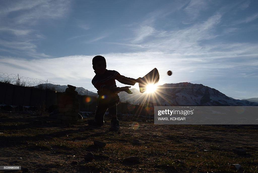 TOPSHOT - Afghan children play cricket during sunset near ...