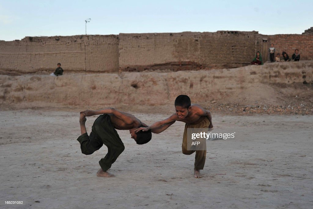 Afghan Children play Ghursai, a traditional boy's game played in the countryside in Jalalabad on April 1, 2013. Children hold one foot in one hand and then try to knock down the other opponent. AFP PHOTO/ Noorullah Shirzada