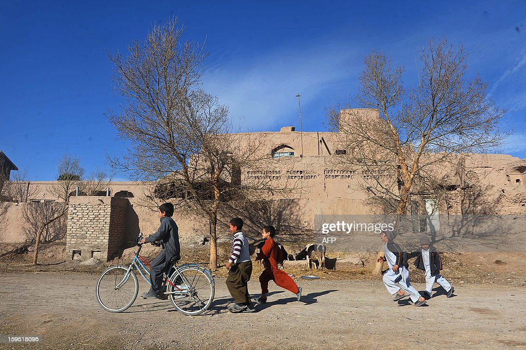 Afghan children play in a street in Herat on January 14, 2013. Over a third of Afghans are living in abject poverty, as those in power are more concerned about addressing their vested interests rather than the basic needs of the population, a UN report said. AFP PHOTO / Aref Karimi