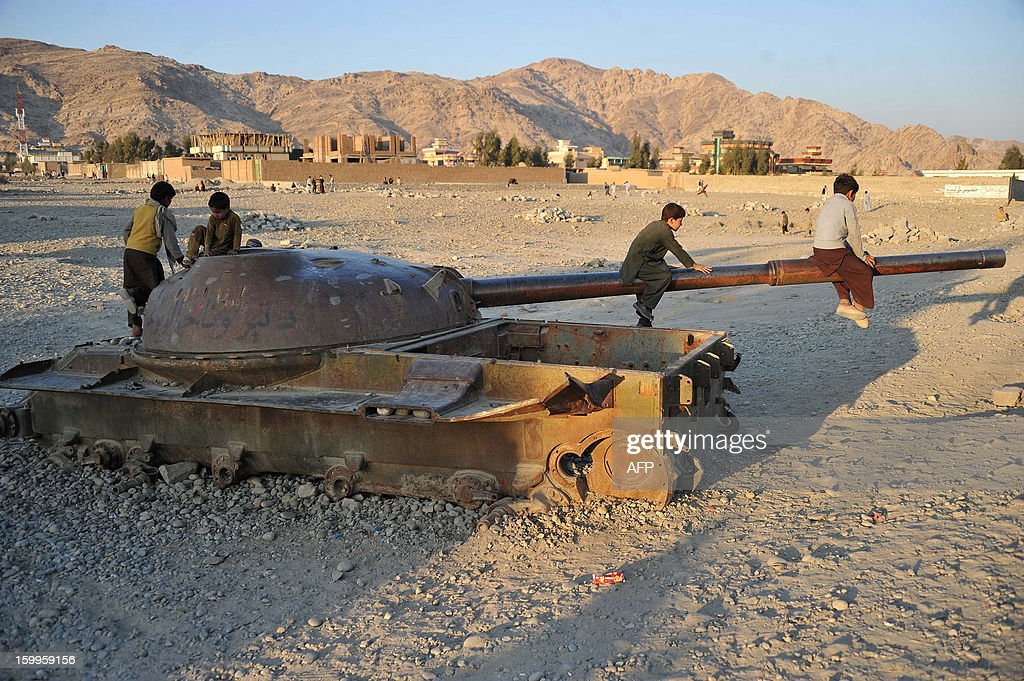 Afghan children play on the remains of a Soviet-era tank in Jalalabad January 23, 2013. Over a third of Afghans are living in abject poverty, as those in power are more concerned about addressing their vested interests rather than the basic needs of the population, a UN report said. AFP PHOTO/ Noorullah Shirzada