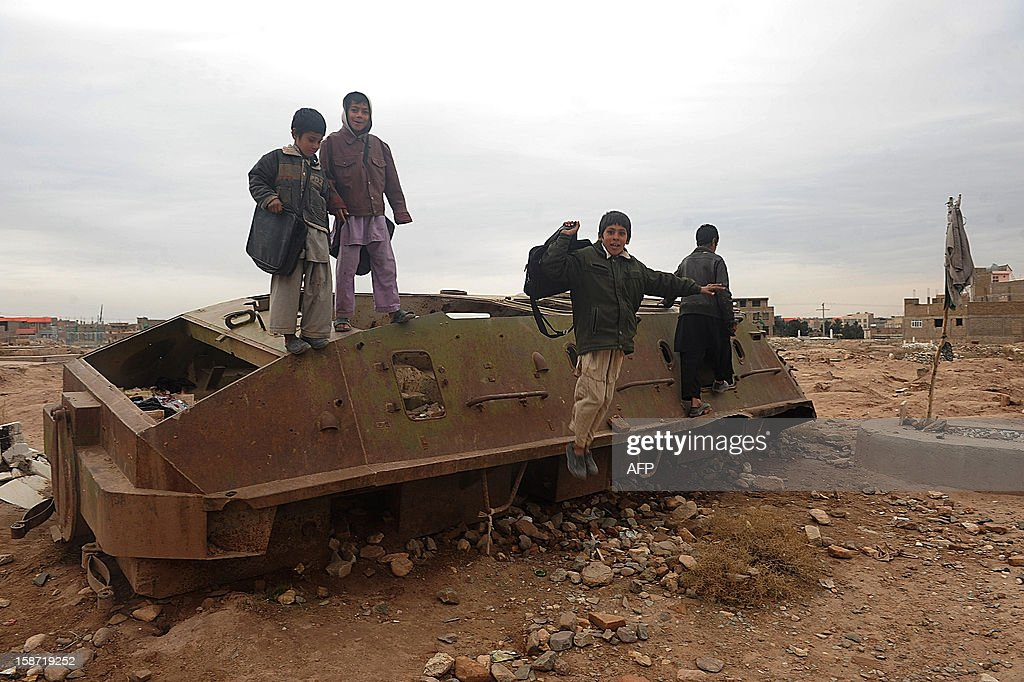 Afghan children play over the remains of a Soviet-era tank in Herat on December 26, 2012, which marks the 33rd anniversary of the Soviets troops invasion of Afghanistan. AFP PHOTO/ Aref Karimi