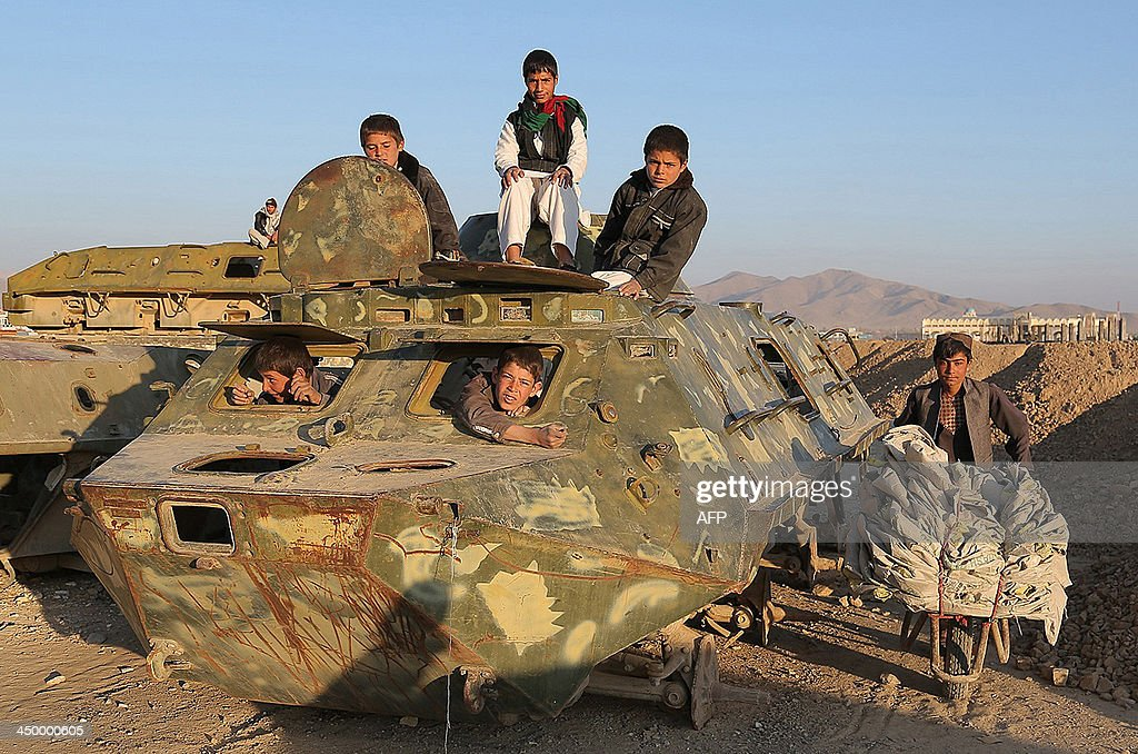 Afghan children play over the wreckage of an old Soviet-era tank in Ghazni on November 15, 2013. Tens of thousands of children in Afghanistan, driven by poverty, work on the streets of the war-torn country's cities and often fall prey to Taliban bombings and other violence, as well as abuse. AFP PHOTO/ Rahmatullah ALIZADA