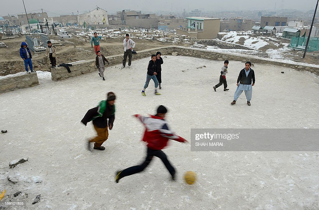Afghan children play soccer on a cold day in Kabul on January 8, 2013. Despite Afghanistan receiving billions of dollars of aid since 2001, more than 100 children died last year during the harshest winter in two decades, and the UN refugee agency UNHCR has co-ordinated efforts to reduce repeat fatalities. AFP PHOTO/ SHAH Marai
