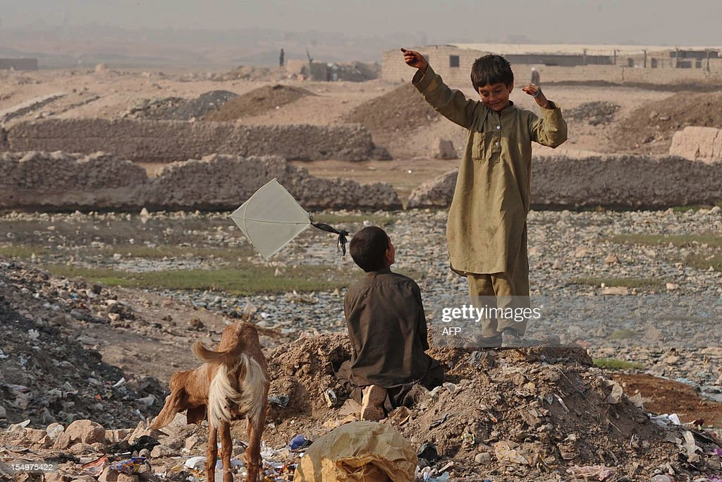 Afghan children play with a kite at a landfill in Herat on October 29, 2012. Over a third of Afghans are living in abject poverty, as those in power are more concerned about addressing their vested interests rather than the basic needs of the population, a UN report said. AFP PHOTO/Aref KARIMI