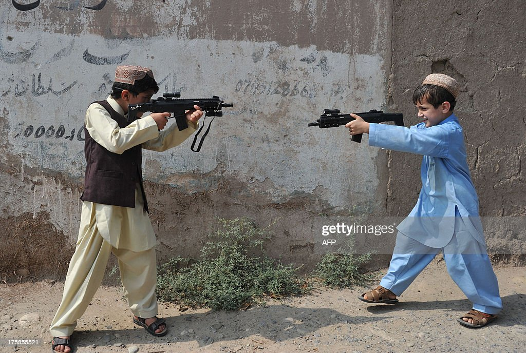 Afghan children play with plastic toy guns during the ...