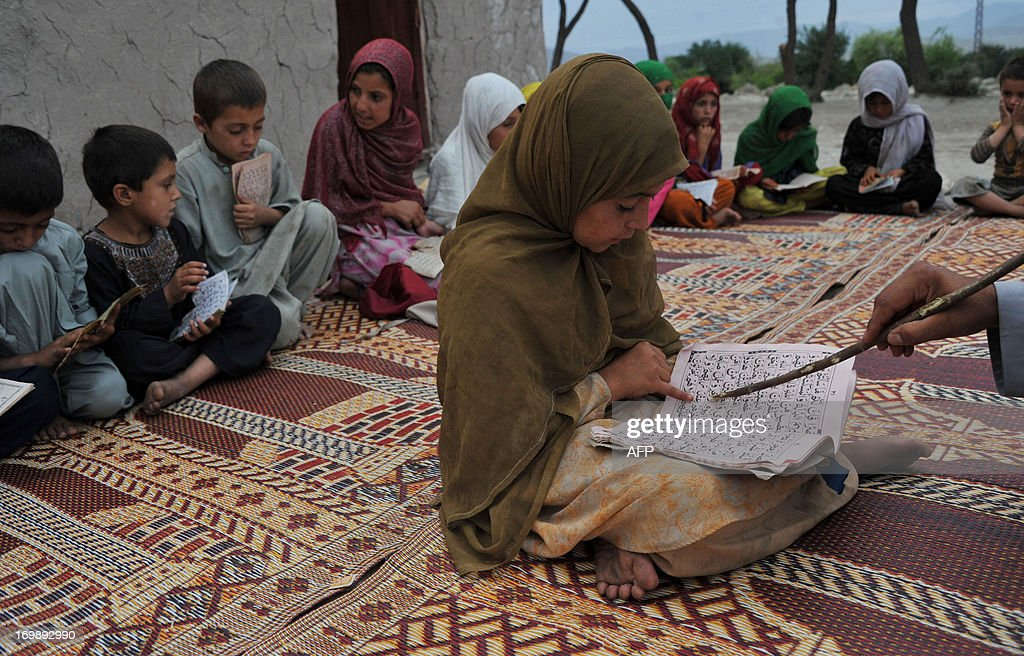 Afghan children read the Quran at a mosque in the outskirt of Jalalabad on June 4, 2013. Tens of thousands of children in Afghanistan, driven by poverty, work on the streets of the war-torn country's cities and often fall prey to Taliban bombings and other violence, as well as abuse. AFP PHOTO/Noorullah Shirzada