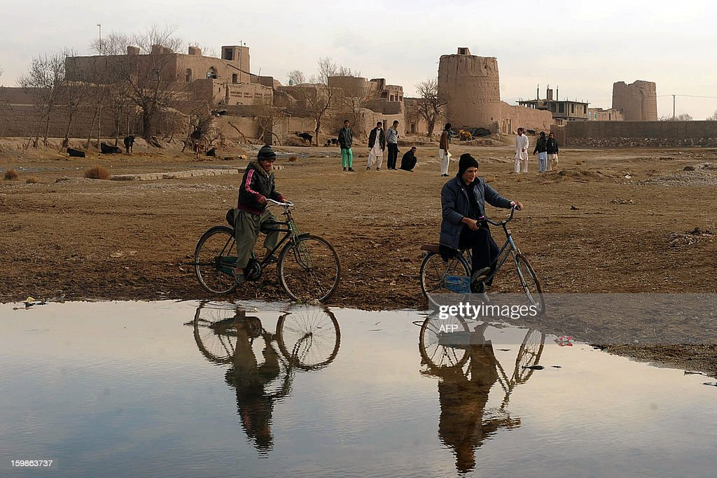 Afghan children ride their bikes near a river on the outskirts of Herat on January 21, 2013. Over a third of Afghans are living in abject poverty, as those in power are more concerned about addressing their vested interests rather than the basic needs of the population, a UN report said. AFP PHOTO / Aref Karimi