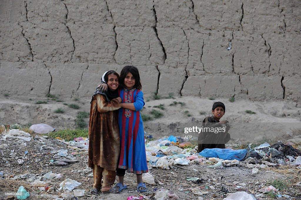 Afghan children search the garbage to find some useful items as they look on during Children's Day in Mazar-i Sharif on June 1, 2013. Tens of thousands of children in Afghanistan, driven by poverty, work on the streets of the war-torn country's cities and often fall prey to Taliban bombings and other violence, as well as abuse. AFP PHOTO/ Farshad USYAN