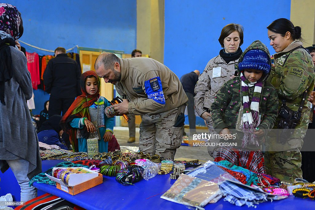 Afghan children sell handicraft items to NATO soldiers during a monthly bazaar at the International Security Assistance Force (ISAF) headquarters in Kabul on January 5, 2013. Analysts have warned the country could plunge into another large-scale civil war after the NATO-led force departs by 2015. AFP PHOTO / Massoud HOSSAINI