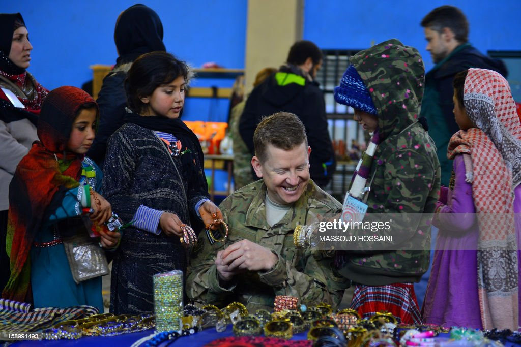 Afghan children sell handicraft to a NATO soldier during a monthly bazaar at the International Security Assistance Force (ISAF) headquarters in Kabul on January 5, 2013. Analysts have warned the country could plunge into another large-scale civil war after the NATO-led force departs by 2015. AFP PHOTO / Massoud HOSSAINI