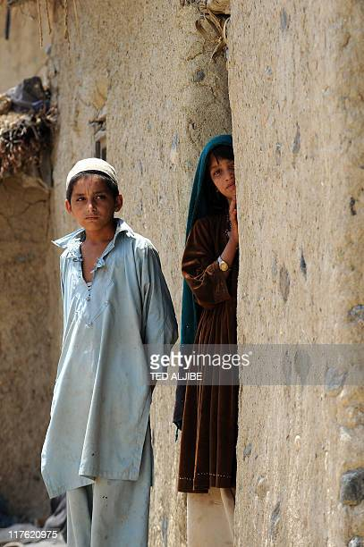 Afghan children stand at the entrance of their house at a village in Sabari district in eastern Khost province on June 24 2011 AFP PHOTO/TED ALJIBE