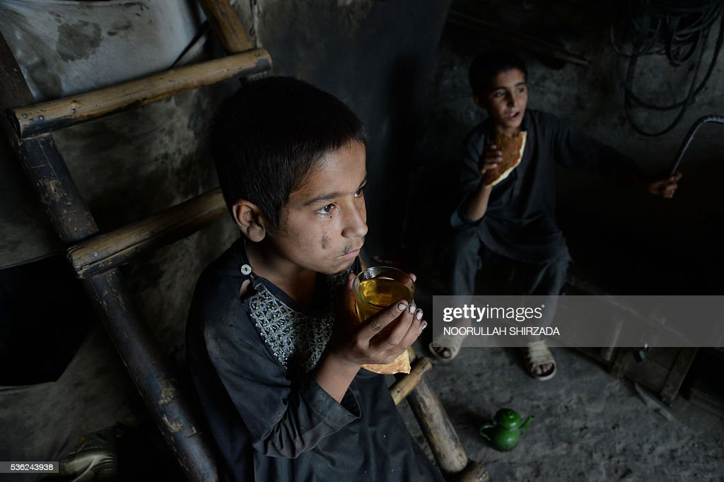 Afghan children take rest from their work at a mechanics shop in Jalalabad, eastern Nangarhar province, during Children's Day on June 1, 2016. Tens of thousands of children in Afghanistan, driven by poverty, work on the streets of the war-torn country's cities and often fall prey to Taliban bombings and other violence, as well as abuse. / AFP / NOORULLAH