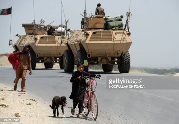 TOPSHOT Afghan children walk past security force personnel as they leave a village during an operation against Islamic State militants in the...