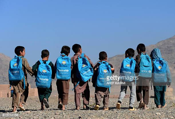 TOPSHOT Afghan children walk to school on the outskirts of Herat on October 10 2016 / AFP / AREF KARIMI