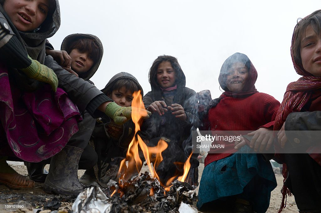 Afghan children warm-up themselves around fire on a cold day in Kabul on January 8, 2013. Despite Afghanistan receiving billions of dollars of aid since 2001, more than 100 children died last year during the harshest winter in two decades, and the UN refugee agency UNHCR has co-ordinated efforts to reduce repeat fatalities. AFP PHOTO/ SHAH Marai