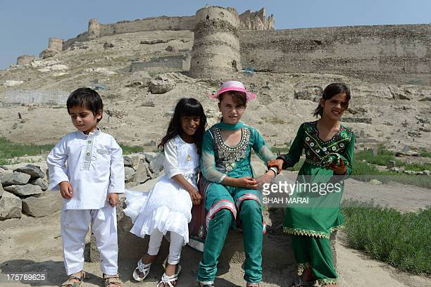 Afghan children wearing new clothes which is an Eid alFitr tradition look on during the festival which marks the end of the fasting month of Ramadan...