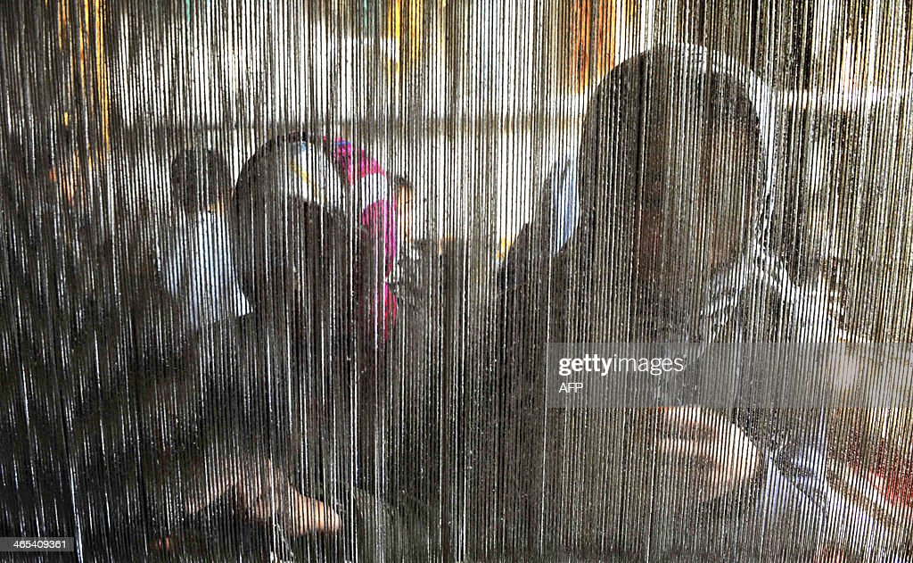 Afghan children weave a carpet at a traditional carpet factory in Herat on January 27, 2014. Some nine million Afghans or 36 percent of the population are living in 'absolute poverty' while another 37 percent live barely above the poverty line, according to a UN report. AFP PHOTO/Aref Karimi