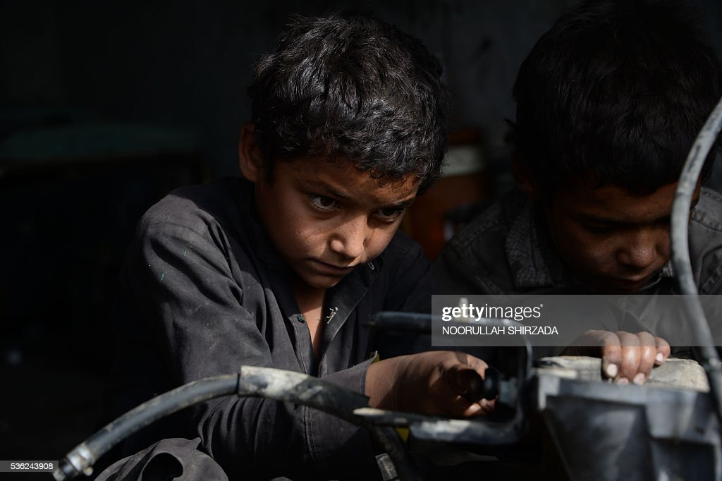 Afghan children work at a mechanics shop in Jalalabad, eastern Nangarhar province, during Children's Day on June 1, 2016. Tens of thousands of children in Afghanistan, driven by poverty, work on the streets of the war-torn country's cities and often fall prey to Taliban bombings and other violence, as well as abuse. / AFP / NOORULLAH