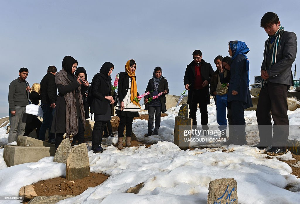 Afghan civil society activists pay their respects and participate in a ceremony over the grave of Shakila, an ethnic Hazara girl who was allegedly raped and killed by a member of Bamiyan's provincial council one year ago, on the outskirsts of Kabul on January 26, 2013. The Afghan attorney general did not proceed on Shakila's case, her brother Mahammad Alam said. AFP PHOTO/Massoud HOSSAINI