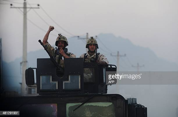 Afghan commandos exult as they ride on top of a humvee as they leave the Afghan Election Commission complex at the end of a firefight with insurgents...