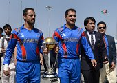 Afghan cricket captain Mohammad Nabi Eisakhil and batsman Nawroz Mangal carry the 2015 Cricket World Cup trophy as members of the National Cricket...