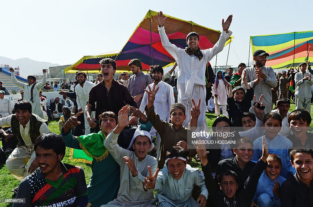 Afghan cricket fans celebrate runs by their team as they watch the Afghanistan and Kenya match on a screen at the International Cricket Stadium in Kabul on October 4, 2013. War-torn Afghanistan erupted in wild celebrations as its cricket team beat Kenya to qualify for the 2015 World Cup, just 12 years after the game took hold in the wake of the Taliban's fall. AFP PHOTO/ Massoud HOSSAINI