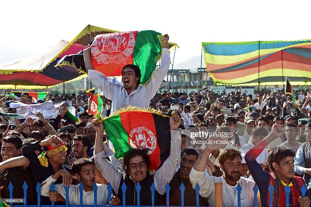 Afghan cricket fans celebrate their teams victory in the match between Afghanistan and Kenya as they watch it on a big screen at the International Cricket Stadium in Kabul on October 4, 2013. War-torn Afghanistan erupted in wild celebrations as its cricket team beat Kenya to qualify for the 2015 World Cup, just 12 years after the game took hold in the wake of the Taliban's fall. AFP PHOTO/ Massoud HOSSAINI