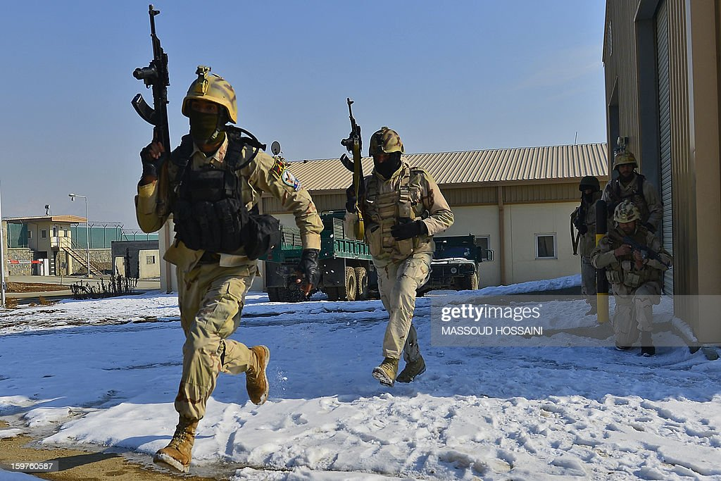 Afghan Crisis Response Unit (CRU) forces perform a house entry drill during an exercise at their camp on the outskirts of Kabul on January 20, 2013. The Afghan Crisis Response Unit (CRU) are trained by US and British forces with the task of counter-terrorism and drug enforcement duties in the country. AFP PHOTO/MASSOUD HOSSAINI