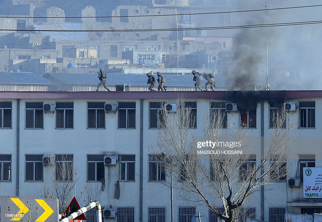 Afghan Crisis Response Unit (CRU) members run on the top of the roof of the Kabul police headquarters during a clash between Afghanistan forces and Taliban fighters in Kabul on January 21, 2013. Three police officers and three suicide bombers have been killed in an ongoing attack on a police complex in the Afghan capital Kabul, which has already lasted more than six hours, officials said. NATO troops joined a fight against a Taliban suicide squad that stormed a Kabul police headquarters, unleashing a stand-off that lasted for more than five hours. AFP PHOTO/ Massoud HOSSAINI