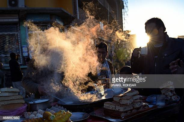 Afghan customers drink hot milk and eat breakfast with cookies at a roadside stall in a market in Kabul on April 8 2015 AFP PHOTO / Wakil Kohsar