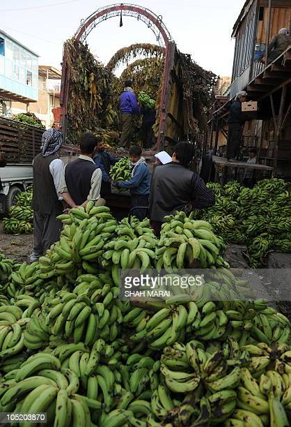 Afghan day laborers unload bananas from a truck at the vegetable market in Kabul on October 12 2010 Afghanistan is one of the world's poorest...