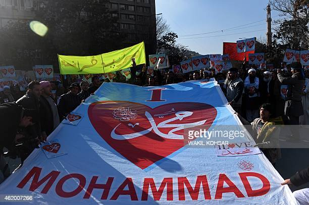Afghan demonstrators chant slogans while holding a banner and placards that read 'Muhammad' during a protest against the printing of satirical...